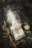 Flour el bolso, los oídos del trigo y la taza de medición en negro Fotografía de archivo libre de regalías