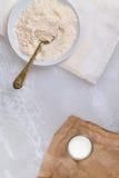 Flour em uma bacia com uma colher, e leite em um vidro Foto de Stock