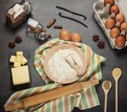 Flour en cuenco en la toalla, los huevos, la mantequilla y las especias para la pasta, en gris imágenes de archivo libres de regalías