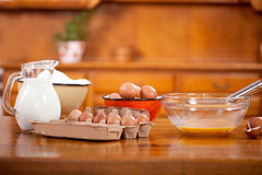 Flour en egs y jarro de la cucharada del cuenco con leche Foto de archivo