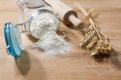 Flour en el tarro de cristal con el rodillo y las gavillas de trigo Imágenes de archivo libres de regalías