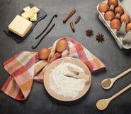 Flour en la placa, los huevos y la mantequilla, especias, en superficie de trabajo imagen de archivo libre de regalías