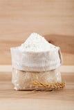 Flour en un bolso de la lona y un oído del trigo en el de madera Fotografía de archivo
