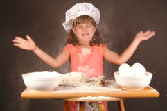 Flour everywhere. A cute young girl clapping her hands and getting flour everywhere while making cookies stock photo