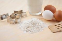 Flour, Glas Milch, wischen Sie, bildet sich Plätzchenschneider und eggs anflehen an Stockfoto