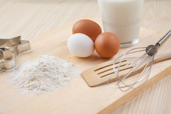 Flour, glass of milk, whisk, Cookie cutter forms and eggs on woo Stock Photos