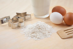 Flour, glass of milk, whisk, Cookie cutter forms and eggs on woo Stock Photo