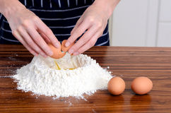 Flour hands eggs raw ingredients. Close up of chef's hands with plain flour well and eggs in preparation process for baking, cooking, pastry making Royalty Free Stock Photography