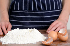 Flour hands eggs raw ingredients. Close up of chef's hands with plain flour well and eggs in preparation process for baking, cooking, pastry making Stock Photography