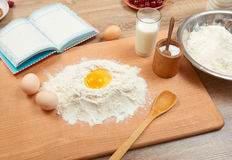 Flour heap and broken egg closeup for baking on a wooden background. Raw food and kitchen utensils. Royalty Free Stock Photo