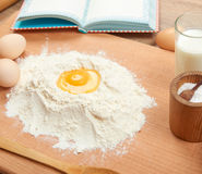 Flour heap and broken egg closeup for baking on a wooden background. Raw food and kitchen utensils. Stock Photos