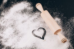 Flour with heart and rolling pin on black Royalty Free Stock Photography