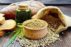 Flour hemp in bowl with bread and oil on dark board royalty free stock photography