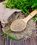 Flour hemp in spoon with leaf and bag on board Stock Photography