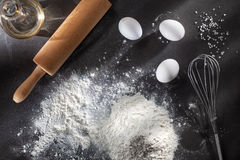 Flour and ingredients on black table Stock Image
