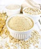 Flour l'avena in ciotole bianche con crusca ed i fiocchi a bordo Fotografie Stock Libere da Diritti