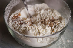 Flour in a large glass bowl. Flour and cinnamon mixed in a large bowl Stock Photo