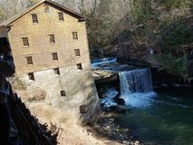 Flour mill with waterfall stock images