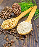 Flour and nuts cedar in spoon on board Stock Photography