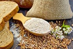 Flour o trigo mourisco na colher com cereais e flor a bordo Fotos de Stock