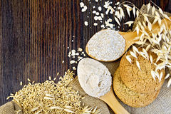 Flour oat with bran in spoons and cookies on board. Flour and bran oaten in a spoons, stalks of oats, grits and biscuits on a background sacking on a wooden Royalty Free Stock Photo