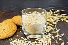 Flour oat in glass with cookies on board Royalty Free Stock Photos