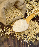 Flour oat in spoon with grains on board Royalty Free Stock Photography