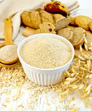 Flour oat in white bowl with bran in spoon on board Stock Image
