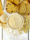 Flour oat in white bowl with bran in spoon on board top Stock Photos