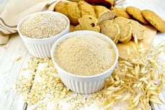 Flour oat in white bowl with bread on board Royalty Free Stock Images