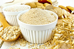 Flour oat in white bowl with flakes in spoon on board. Flour and bran oats in white bowls, oat flakes in a spoon, stalks of oats, bread and biscuits, napkin on a royalty free stock photos