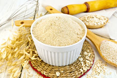Flour oat in white bowl on light board Royalty Free Stock Photos