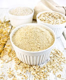 Flour oat in white bowls with bran and flakes on board. Meal oat, bran and oat flakes in three white bowls, oat stalks, towel on a background of wooden boards royalty free stock photos
