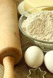 Flour, oil, eggs and rolling pin on sacking Stock Image