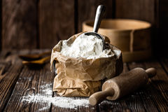 Flour. Paper bag with flour on rustic wooden background stock photo