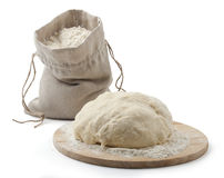 Flour and pastry. A flour in the sack and a pastry on the wooden board Stock Image
