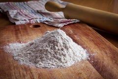 Flour, pino do rolo e toalha na tabela Foto de Stock