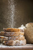 Flour poured on slices of bread. White flour poured on four slices of fresh healthy bread on brown background looking delicious Stock Photography