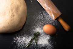 Flour, rolling pin, egg, rosemarin and dough for pie Royalty Free Stock Photo