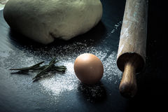 Flour, rolling pin, egg, rosemarin and dough for pie. Toned Stock Photo