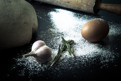 Flour, rolling pin, egg, rosemary, garlic and dough for pie. Ton Stock Image
