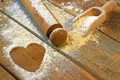 Flour, rolling pin and heart with wood background Royalty Free Stock Image