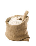 Flour Sack. Burlap sack of wholemeal bread flour with wooden scoop on white background Royalty Free Stock Photography
