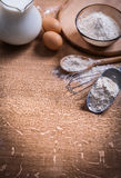 Flour in scoop spoon and bowl eggs pitcher milk on Royalty Free Stock Images