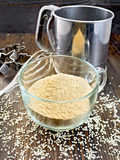 Flour sesame in cup with sieve on dark board Stock Photo