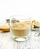 Flour sesame in glassful on board Royalty Free Stock Images