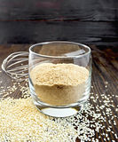 Flour sesame in glassful on dark board Stock Images