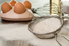 Flour in a sieve  on kitchen table. Stock Image