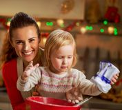 Flour smeared mother and baby making christmas cooki Stock Image