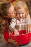 Flour smeared mother and baby making cookies Stock Photos